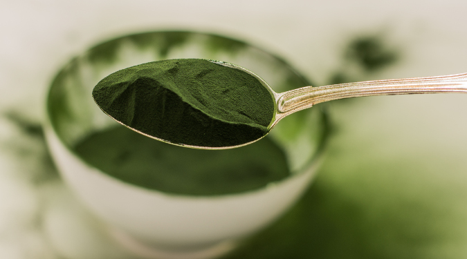 A spoon full of Chlorella over a filled bowl.