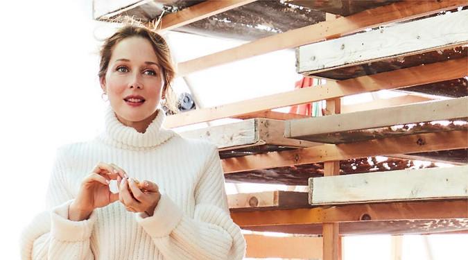 Tata Harper dressed in white beside a rustic wooden farm structure.