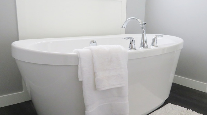 A white bathtub with a towel draped on it.