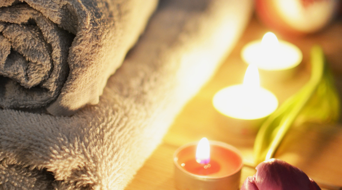 Spa towels with lighted candles.
